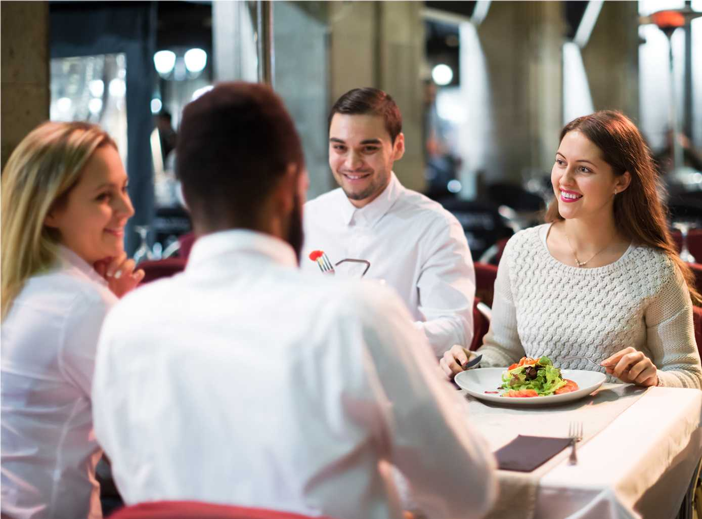 Two young couples happily eating out